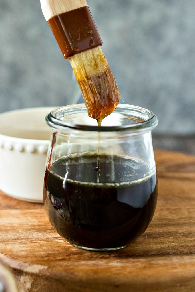 Jar of brown sugar bourbon syrup with a brush dipped in it