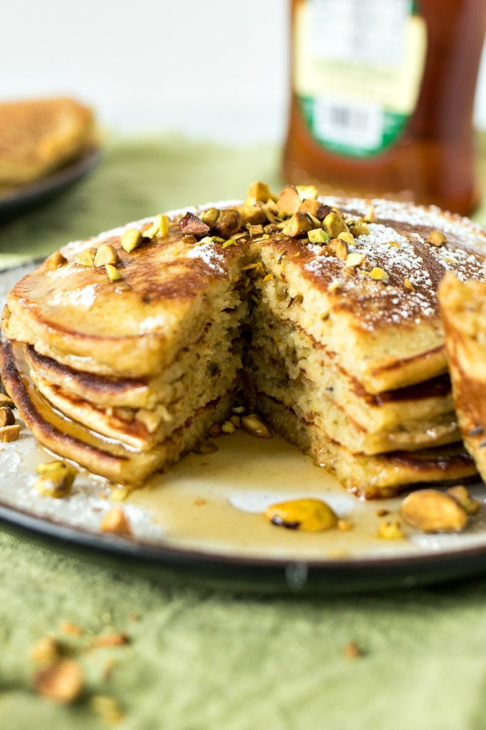 Pistachio Pancakes covered in syrup and crushed pistachios
