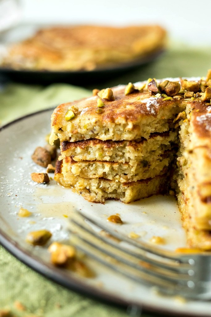 Closeup of a stack of Pistachio Pancakes with a fork in front