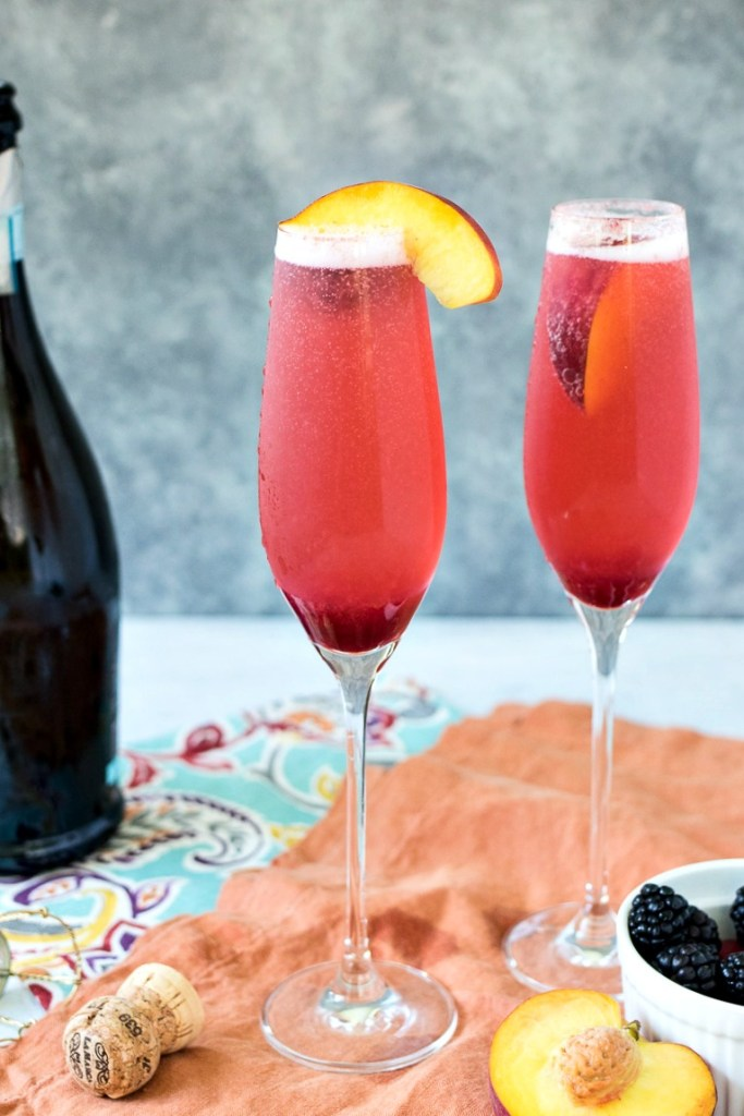 Two champagne flutes of Summer Fruit Bellini topped with a peach slice