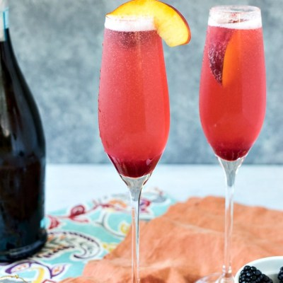 zoomed out shot of two glasses of summer fruit bellinis with peach slices for garnish