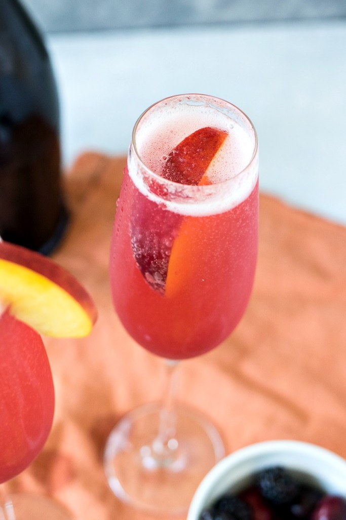 Over head view of the Summer Fruit Bellini glass with a peach slice