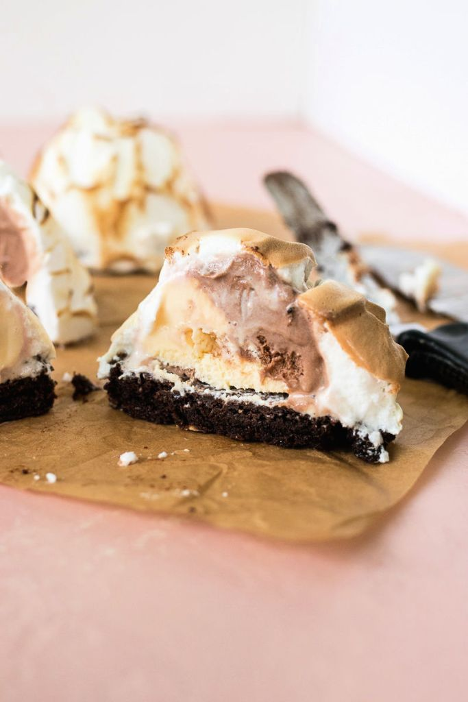 Ice cream is placed on top of a brownie, covered in sweet meringue, and toasted cut in half to show the inside