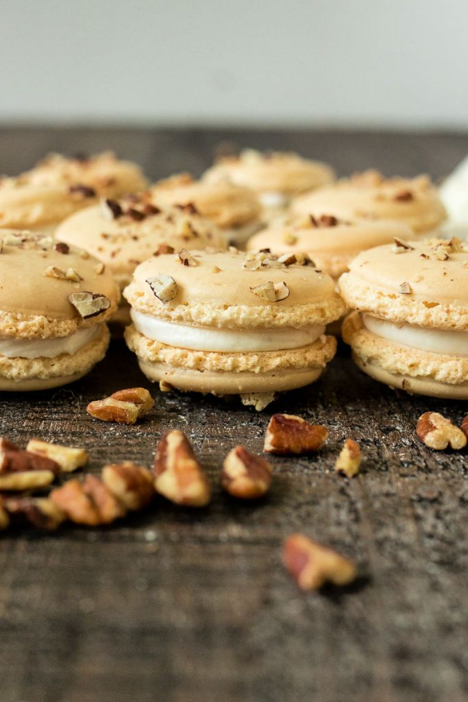 butter pecan macarons with crushed pecans spread in front of them, shot from the front