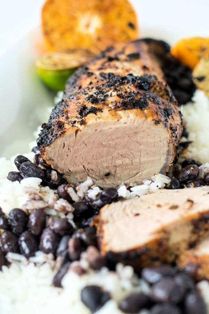 zoomed in shot of sliced mojo pork tenderloin on a bed of rice and black beans with citrus fruit in the background