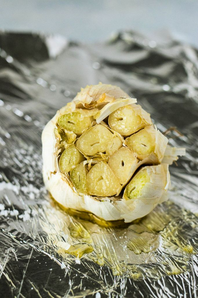zoomed in shot of garlic bulb with olive oil on a piece of foil before it's roasted