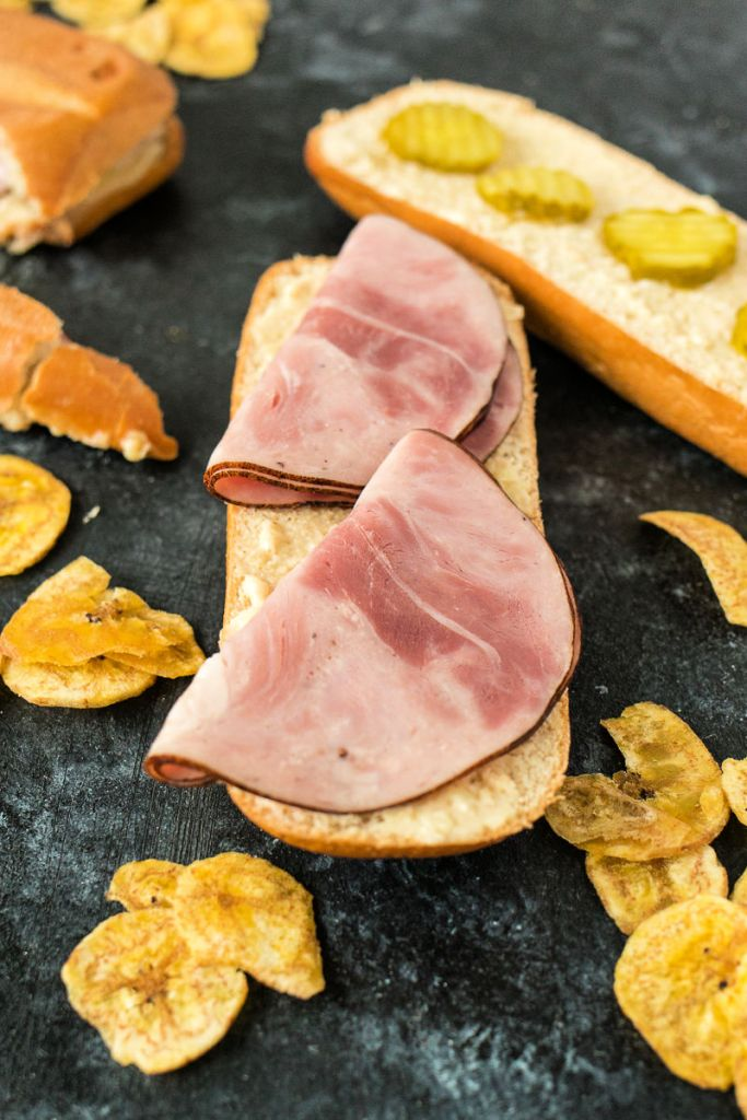 process shot of Cuban sandwich assembly with bread with sliced ham in the foreground and bread with pickles in the background, surrounded by plantain chips