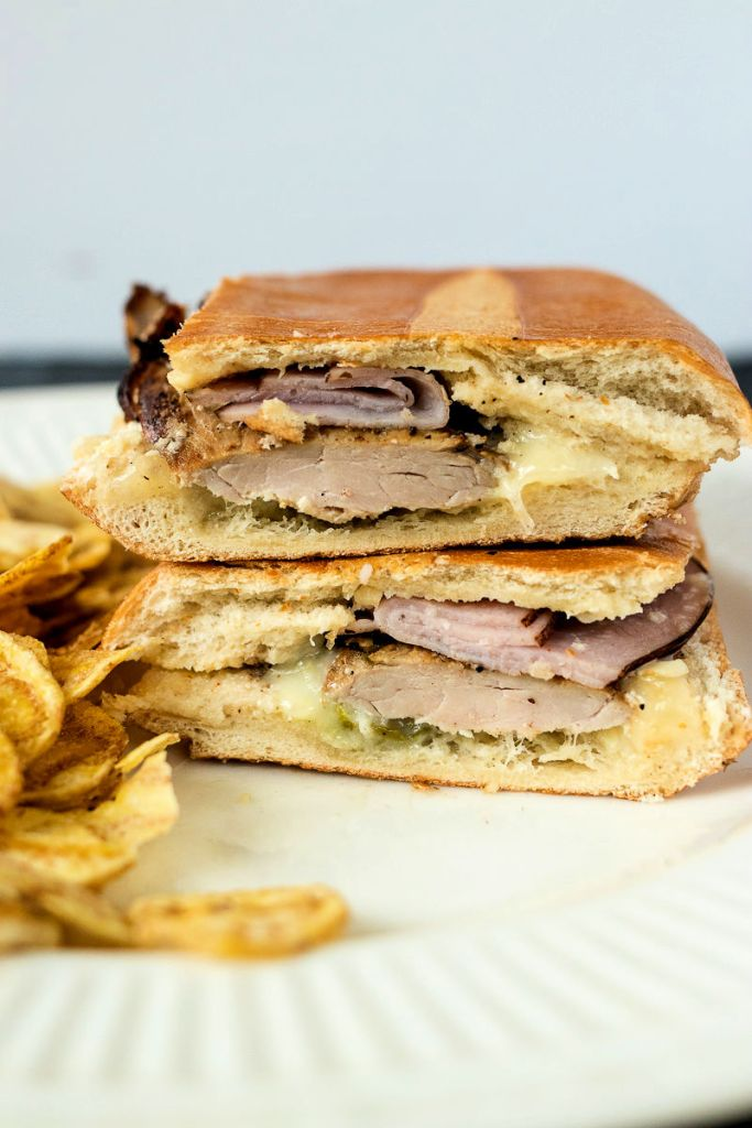 zoomed direct shot of a Cuban sandwich cut in half with the two halves stacked on top of each other, sitting on a plate with plantain chips