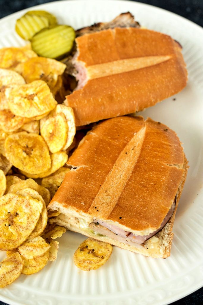 overhead shot of a Cuban sandwich cut in two halves sitting on a plate with plantain chips