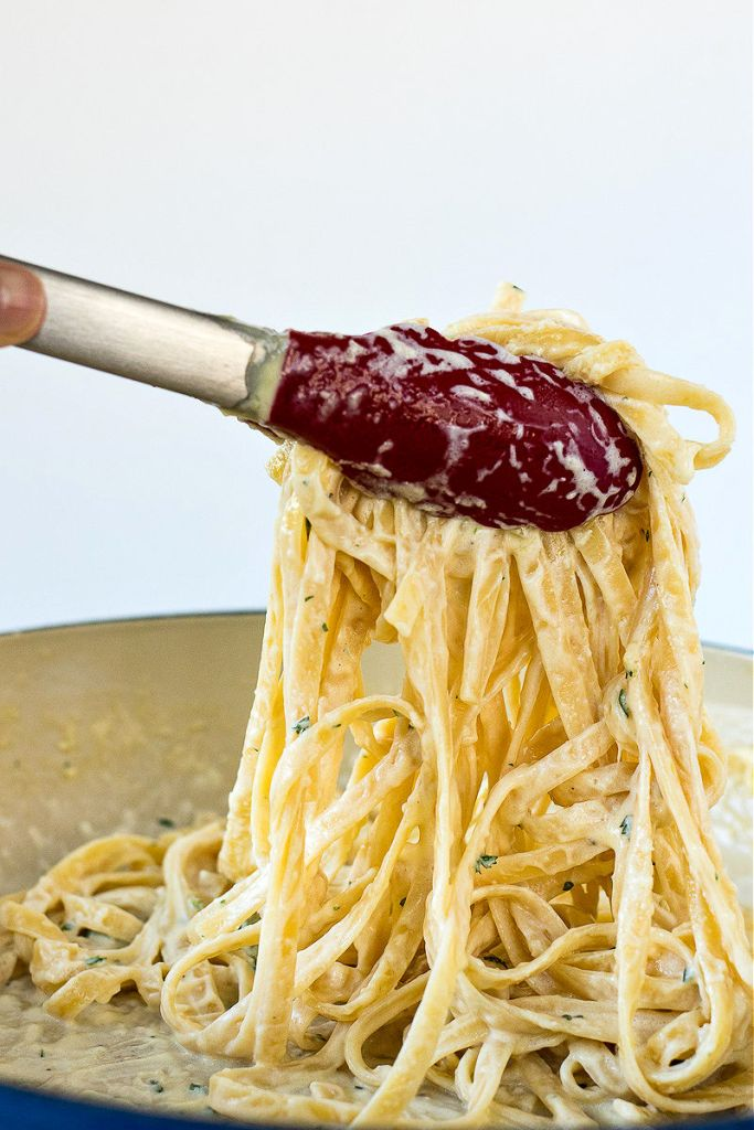 shot of fettuccine alfredo being lifted from pan with a pair of tongs