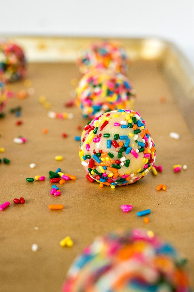 zoomed shot of ball of sugar cookie dough rolled in sprinkles sitting on a baking sheet with other balls of dough