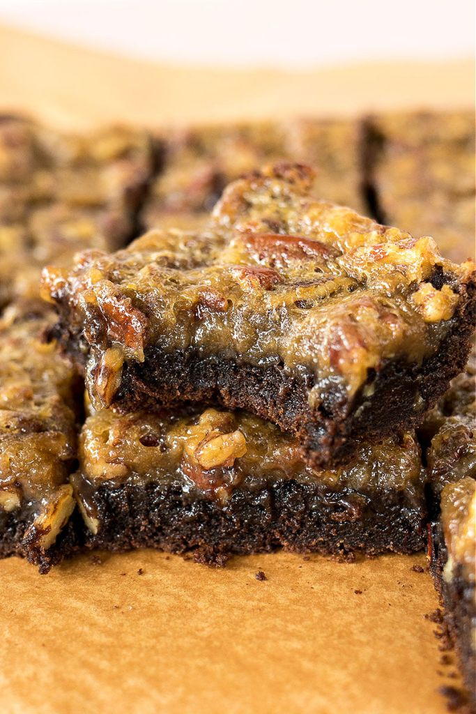 zoomed shot of pecan pie brownies, which one missing a bite and stacked on top of another
