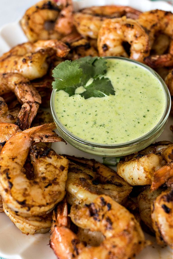 angled shot of serving platter of spicy shrimp with focus on cilantro dipping sauce