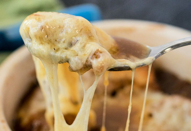 photo of bowl of french onion soup with a spoonful of melted cheese pulling away from it