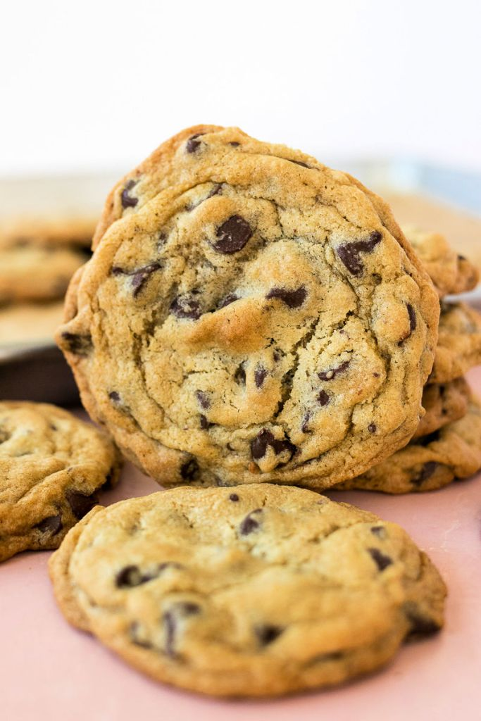 photo of chocolate chip cookie standing  against a stack of more cookies