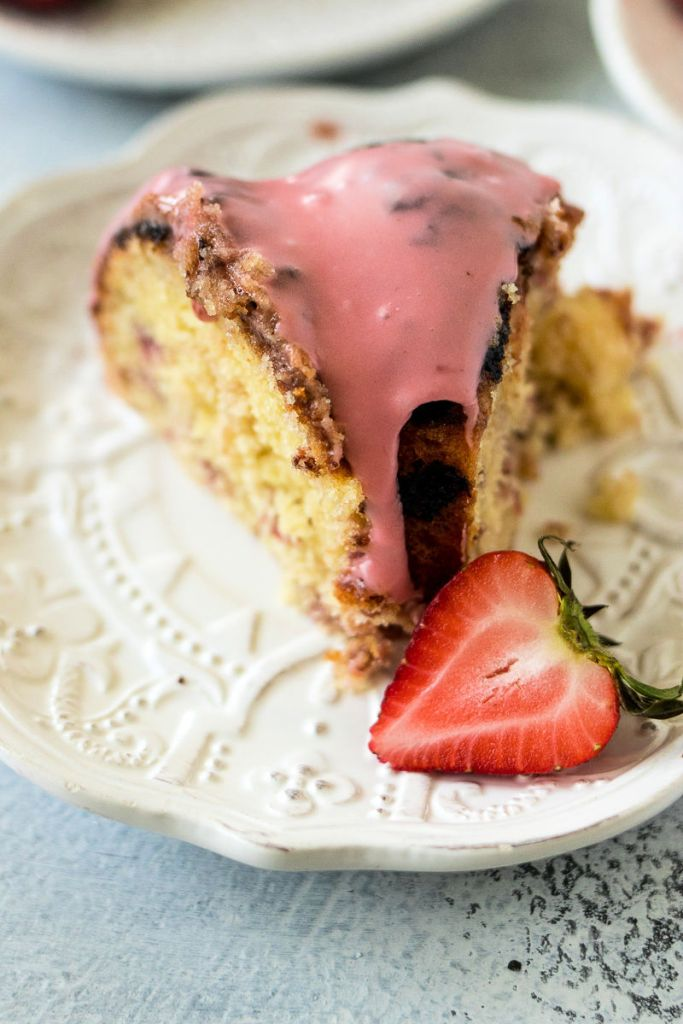 slice of roasted strawberry bundt cake on a plate taken from the front to showcase the pink strawberry icing on top
