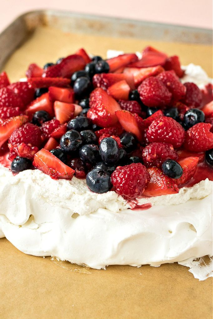 close up of berry pavlova sitting on a baking sheet with parchment paper