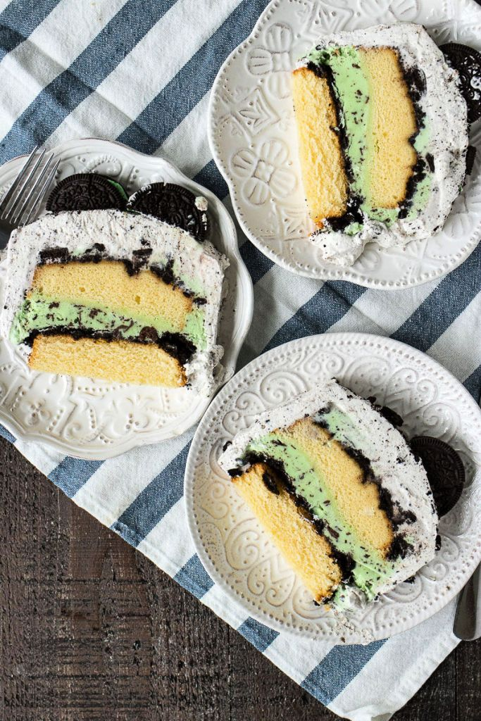 overhead shot slices of mint cookie ice cream cake on three separate plates sitting on a stripped napkin