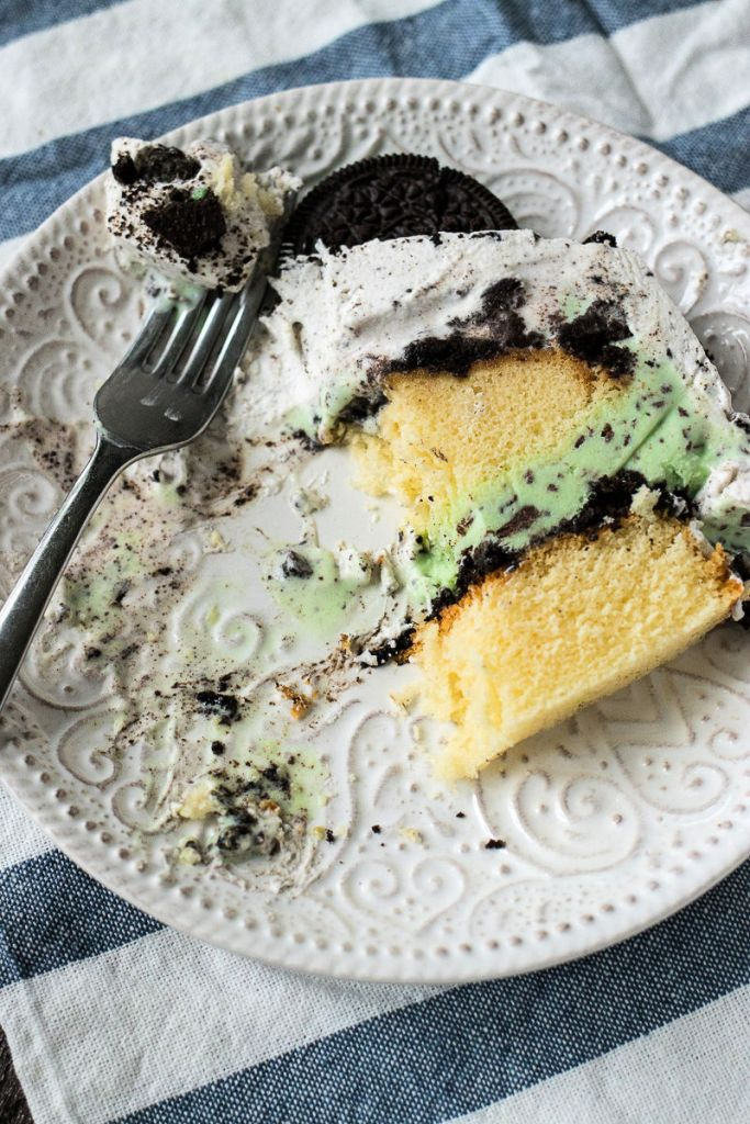 overhead shot of a slice of mint cookie ice cream cake on a plate with half of it eaten