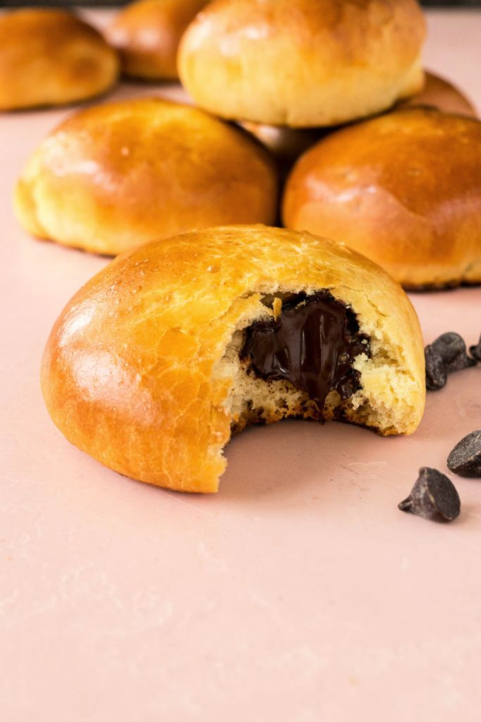 brioche au chocolat bun with a bite removed and more buns in the background