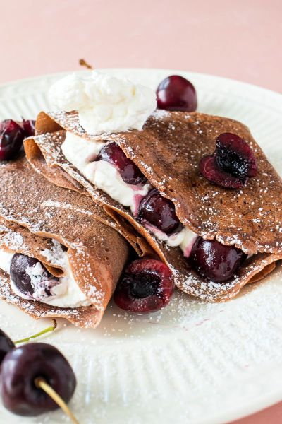 two chocolate cherry crepes on a plate with powdered sugar dusted on top