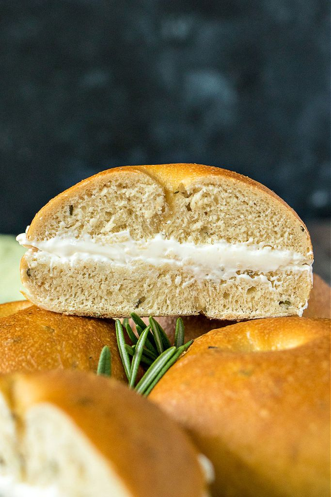 rosemary and olive oil bagel sandwiched with cream cheese sitting atop other bagels