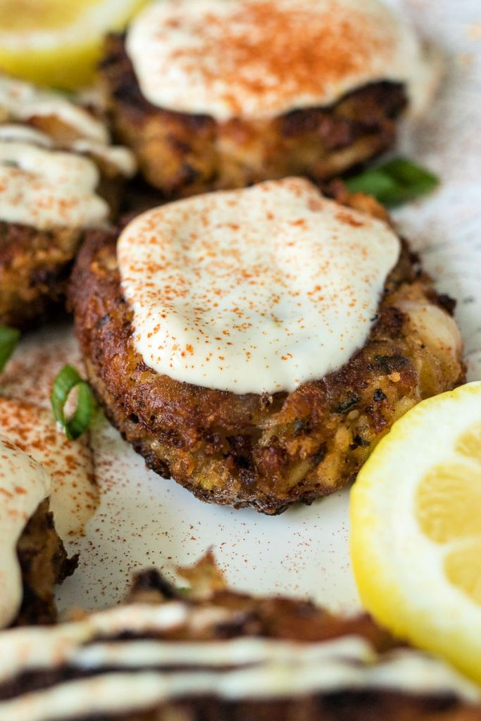 shrimp crab cake with a layer of garlic aioli on top and a sprinkle of paprika