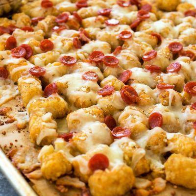 angled photo of pepperoni totchos on a baking sheet and marinara sauce