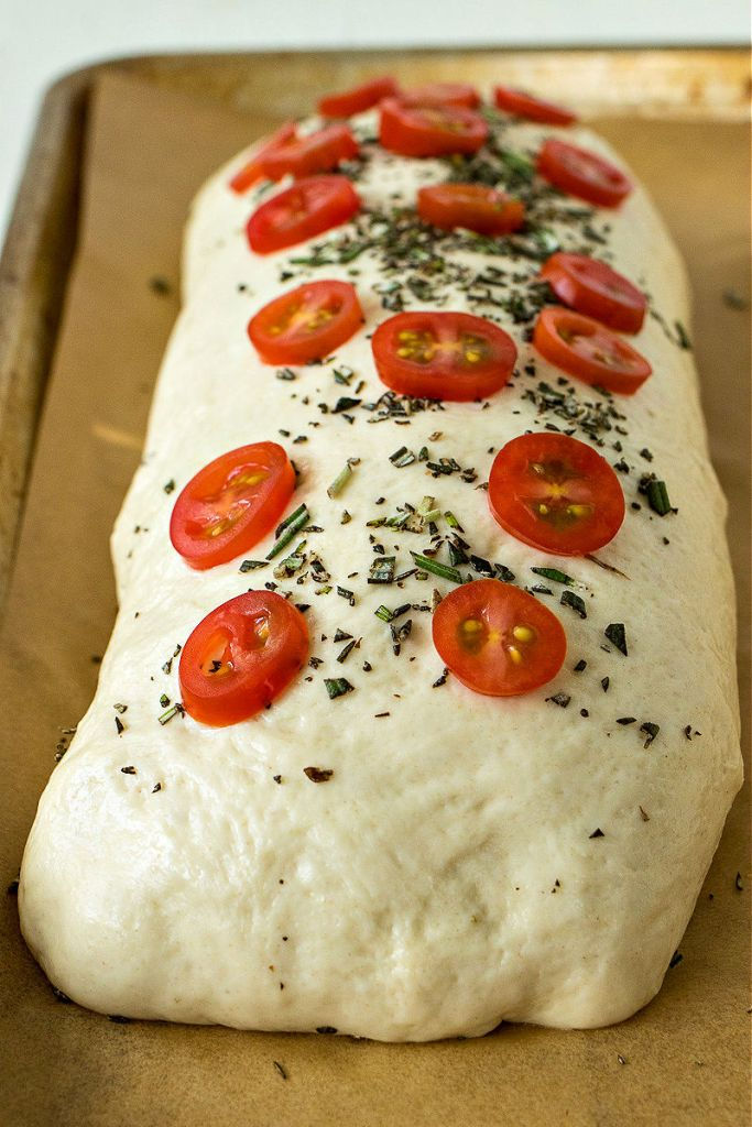 uncooked loaf of salami and cheese, topped with tomatoes and fresh rosemary