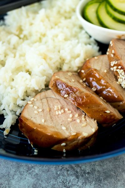 close up of chinese bbq pork tenderloin on a blue plate with rice and pickled cucumbers