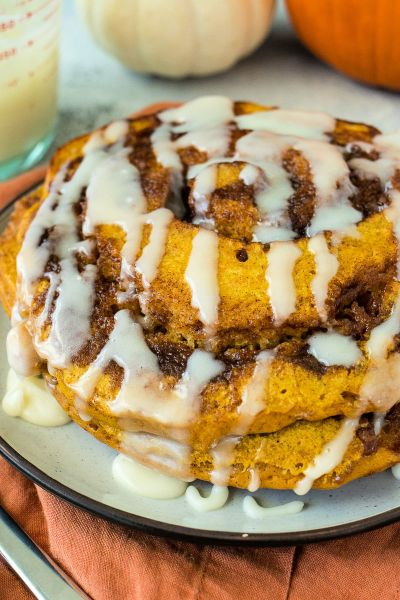 close up angle of pumpkin cinnamon roll pancakes stacked on a white plate