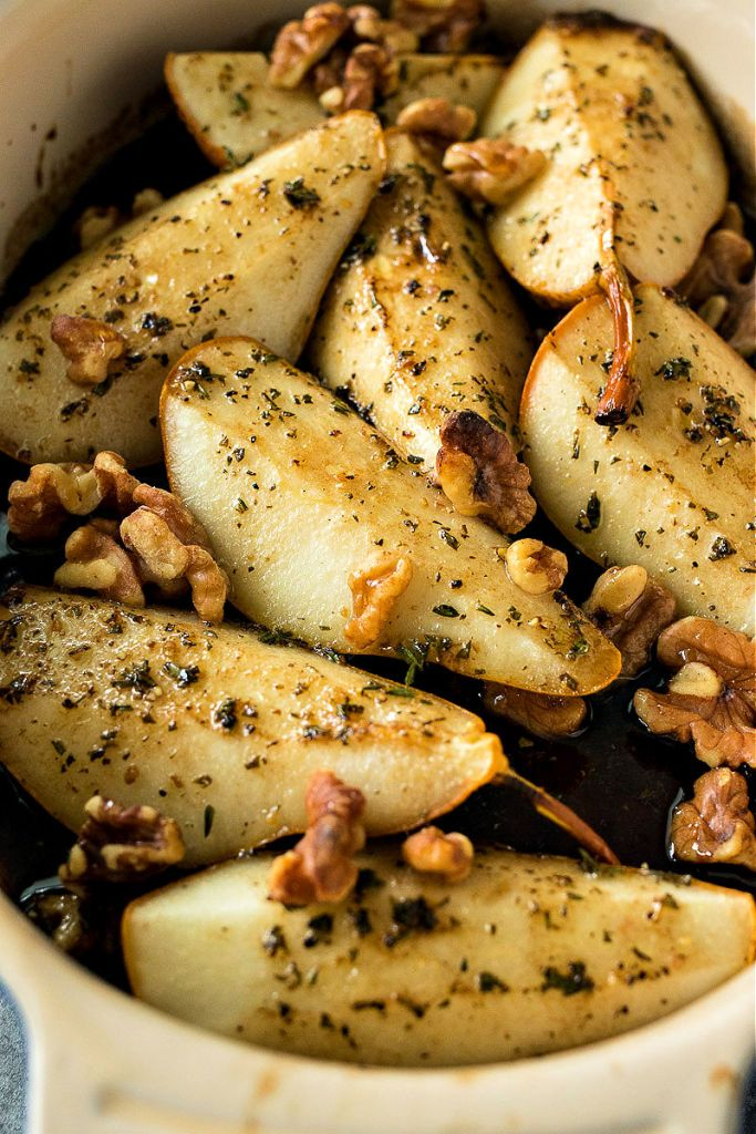 close up of roasted pears sitting in a baking dish with walnuts and roasting liquid
