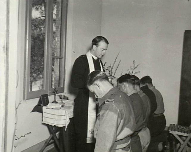 """Aprile 1945, l'anglicano Padre Bob Davies di Newcastle, da la comunione nella """"Koala Casa"""" (nome originale): il club ricreativo australiano che confina in pineta con gli hangars degli squadroni della RAAF."""