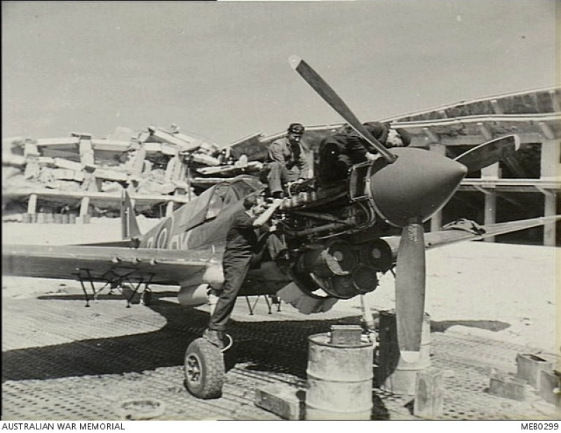 Maggio 1945, durante le fasi finali dell'offensiva di primavera, i cacciabombardieri australiani erano continuamente in aria a sostegno dell'Ottava Armata a Trieste. Il personale di terra RAAF ha fatto la sua parte in modo significativo, montatori e armaioli in particolare, hanno fatto un lavoro splendido e qui sono al lavoro su un Kittyhawk del 450° Squadron RAAF (Desert Harassers). Da sinistra a destra: E. Brown, F. Edwards, L. F. Wilson. Nota: l'edificio in rovina è la Colonia Montecatini.