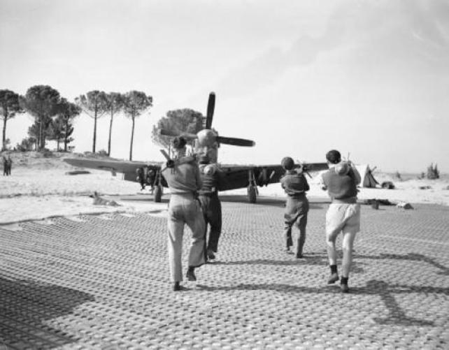 Primavera del 1945, gli armaioli portano 4 bombe da 3 pollici ad un North American Mustang Mark III del 260° Squadron RAF.