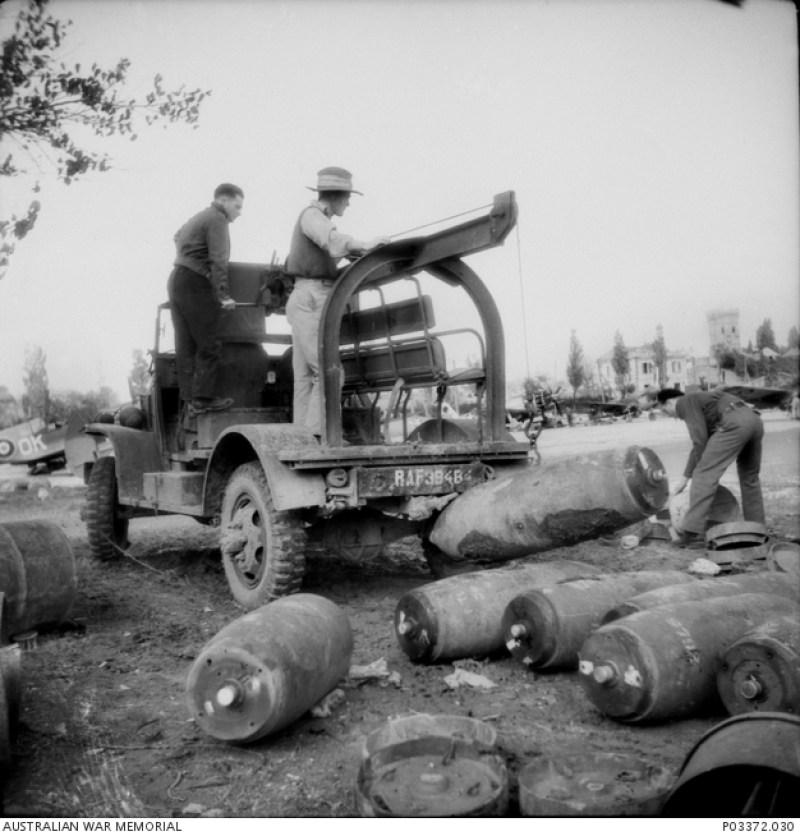 Tre armatori del 450° Squadron RAAF caricano bombe da 500 Libre su un rimorchio.