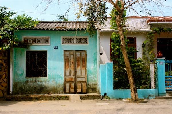 Turquoise house with wooden door and tile roof in Hoi An, Vietnam