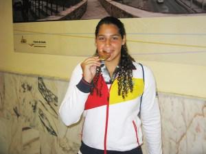 lorena Miranda muerde la medalla de oro conquistada en Barcelona recién llegada a Ceuta