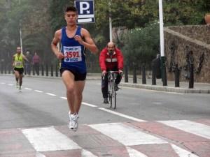 Alfonso Lozano, siguiendo en bicicleta una carrera atlética en los bajos de La Marina
