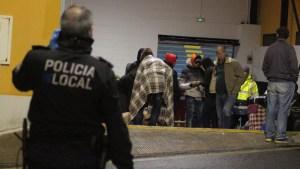 Un policía local observa a un grupo de inmigrantes a las puertas del pabellón de La Libertad