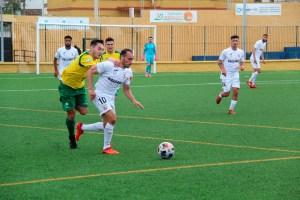 Ismael César, agarrado por un jugador de la UD Los Barrios, en el partido de esta temporada en el 'Pirri'