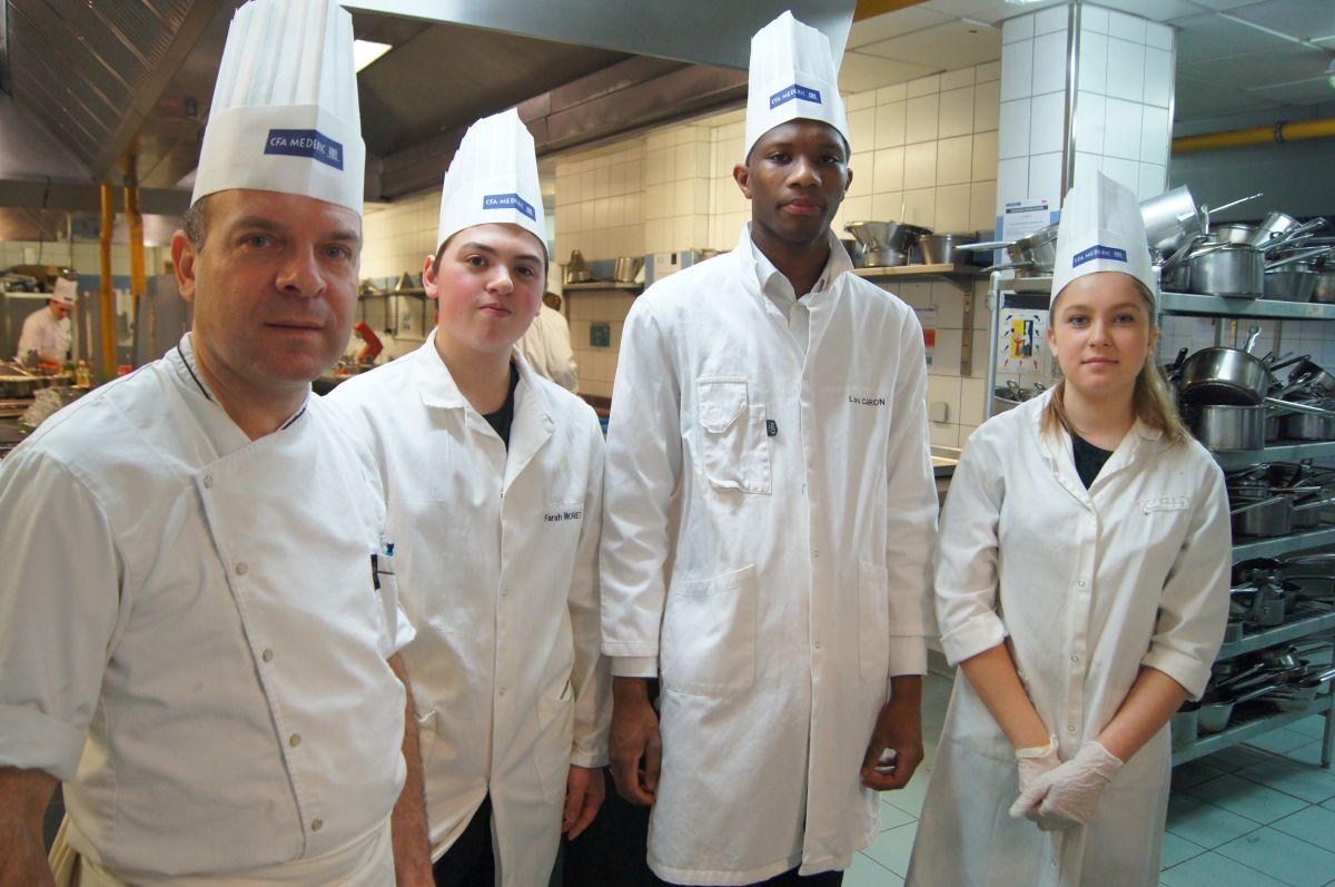 3 jeunes stagiaires en cuisine avec leur formateur
