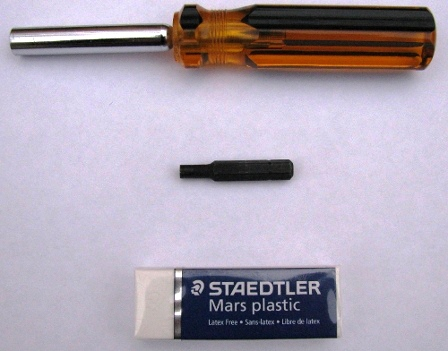 A bit driver, security bit, and Staedtler white plastic eraser.