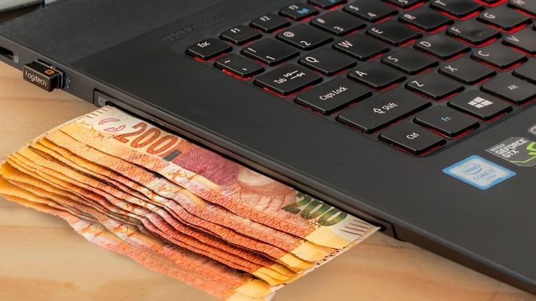 Dinero saliendo de una laptop a manera de cajero