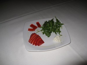 Deconstructed strawberry salad with basil dressed baby arugula, red onions, fresh strawberry, Boursin cheese, and strawberry-red wine vinegar gelée