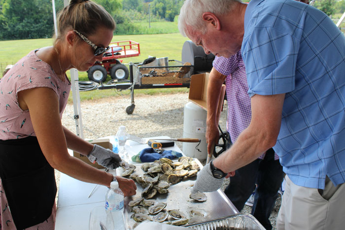 Caterer and Graig Smith shucking oysters