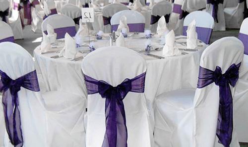 decorative purple sash on white chair covers