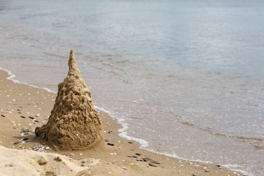 Sand castle destroyed by the surf. Black Sea coast. Space for text.