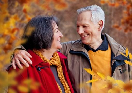 seniors walking in autumn forest / hugging