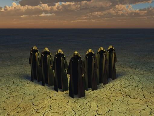 Hooded figures in barren landscape